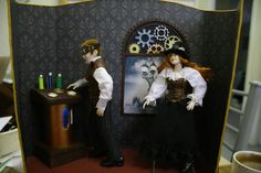 Steampunk mini display. Heidi Ott dolls that I dressed. His vest is leather and his goggles are leather with watch parts. Her corset is leather embellished with watch parts. The hat is a Heidi Ott top hat embellished with watch parts. 1/12 scale