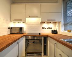 U Shaped Kitchen Design Ideas With White Backsplash And Wood Counter Top Also White Kitchen Cabinet