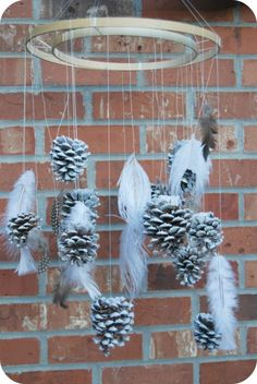 Pinecone Chandelier made using Pine cones, large  medium embroidery hoops and an assortment of feathers! An easy and inexpensive winter craft.