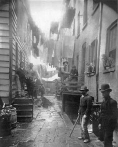 Bandit's Roost. Men in bowler hats stand in the alleyway of a tenement house. Laundry hangs on lines above them.
