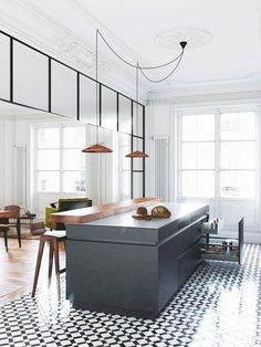 Modern kitchen with classic architectural details, printed tile floors, and rose gold pendant lights