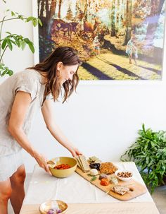 Host of a part setting out a wooden tray of finger foods and snacks