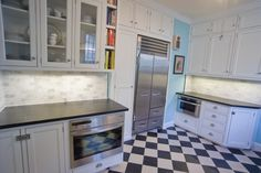 "1920s/Mid-Century Blue Kitchen, Renovation of kitchen in 1920s era house.  Chambers cooktop was kept from the prior renovation done in the 1950s.  The door/panel design of the cabinets is an almost exact copy of the houses original cabinets.  Floor is Marmoleum, bought as sheet and custom cut to period-appropriate 9"" tiles.  Kitchen dimensions are 9.5 x 13 excluding the recess containing the fridge and surrounding cabinets., 27"" built-in Miele Convection/Wall oven, 24"" Sharp microwave…"