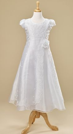 Exquisite organza is accentuated with embroidery throughout the front from top to bottom. Beautiful side drape has a sweet scalloped edge and finishes at the waist with an organza flower. A favorite style for LDS Baptism or First Communion. 100% Polyester Hand wash, drip dry Sizes: 8, 10, 12, 14, 16