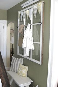 Hang a white window with simple black hooks in a busy hallway as a charming way to store jackets, scarves, and bags. Get the tutorial at My Pink Life.