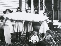 Wisconsin Historical Images  'Melon Party (Without Melons).' Four girls hold an object that resembles a giant slice of watermelon for a photographic mock-up for a photomontage postcard entitled 'Melon Party.' Waupun, Wisconsin. Alfred Stanley Johnson Jr. 1911.