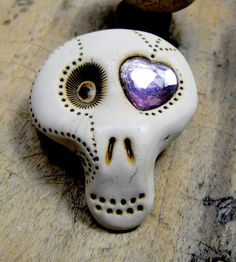 Mini sugar skull brooch with a shiny lavender heart inside his eye