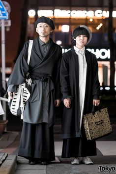 Hatty and Mitsu on the street in Harajuku after dark. Their minimalist looks include items from Yu by Jalan Jalan, Christopher Nemeth, Junya Watanabe for Comme Des Garcons, Vivienne Westwood, CA4LA, George Cox, and IKEA (his bag). Full Looks