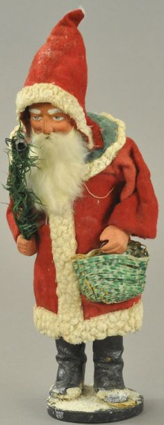 "Impressive looking red robe Santa with green hood trimmed in white, red hood on composition head with rabbit fur beard, basket in one hand, feather tree with candle holder in other, appears to be very old re-gluing at base. 11"" h. (VG - Exc. Cond.)"