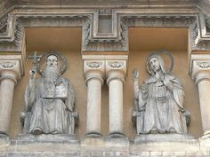 """Statues of St. Benedict and his twin sister, St. Scholastica, above the entrance of the Church of the Annunciation, also called """"St. Gabriel Church"""", in Holečkova Street in Prague-Smíchov, Czechia."""