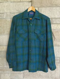 Vintage 1960s mens Pendleton shirt. It is dark green and blue houndstooth plaid. Features a loop collar and two breast pockets with flaps. Made of 100% virgin wool by Pendleton Woolen Mills. Unlined except for across the shoulders. Great vintage condition. No moth holes. Clean and ready to wear.  Labeled Mens size small and fits true to size.  Measurements taken flat: Chest: 40 Shoulder to shoulder: 18 Length: 28 Sleeve length: 23 1/4 Neck: 15 with the collar loop buttoned  Visit Top Spe...