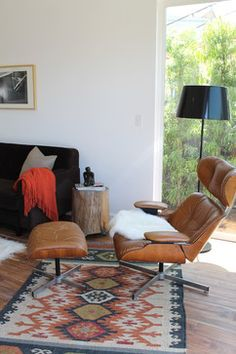 A Madison Modern Home. A dark brown sofa with modern lines, a flokati rug and an MCM coffee table. The tan leather Plycraft lounge chair and ottoman cozy up to a glassed-in corner atop a kilim rug and share space with IKEA's KULLA floor lamp and a log side table.
