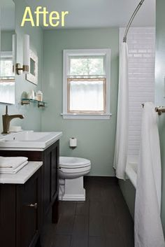 white cubway tiles and light green paint and dark vanity.