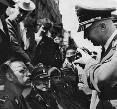 Himmler speaks into a microphone as he meets wounded SS troops back from the front.
