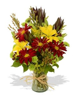A mix of fresh #fallflowers arranged in a glass vase for a natural and rustic look.