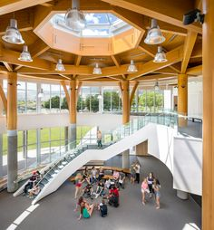 Frank Venables Theatre lobby at the Southern Okanagan Secondary School in Oliver, BC. The lobby boasts supporting concrete columns under large glued laminated beams arranged into a hexagonal shape, finishing in a domed angular skylight at the center, creating a large vaulted airy space with lots of light and bright wood finishes