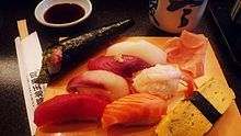 Different types of nigiri-sushi and a long, tapered temaki; pickled gari (ginger) is at the upper right of the serving board