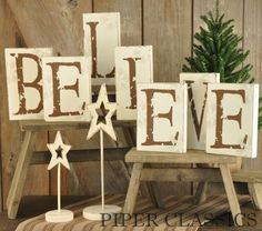 White wooden blocks with brown letters adorned with snowflakes.