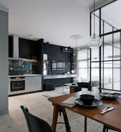 Raw and industrial expression in the kitchen - the raw bricks are painted black to give a cool expression. The wall gives a good contrast to the bright floors, while allowing the kitchen to look timeless and classic.