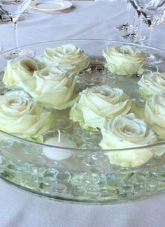 Modern centerpiece on wide glass low cylinder with floating avalanche roses and tealight candles