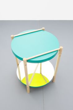 "Village Side Table designed by Lukas Peet | ""The mirrored shelf reflects the bright yellow of the underside of the table, creating a element of surprise as well as the illusion of continuing legs."" 2012 