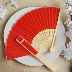 Asian Silk Folding Fans - Red | eFavorMart / Add a classical Asian touch to your wedding, or a special event by presenting your esteemed guests with this special souvenir. Our stylish silk wedding hand fan is intricately handcrafted with a bamboo structure. The framing and spines are crafted from hand-picked bamboo and durably glued with a seamless cut piece of silk to fashion this immaculate magnum opus. Give these swish fans to your respected guests and let them create the lasting memory…