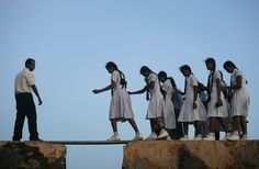 25 Of The Most Dangerous And Unusual Journeys To School In The World.School girls walking across a plank on the wall of the Century Galle Fort in Sri Lanka Kids Going To School, Walk To School, School School, Schools Around The World, Around The Worlds, Sri Lanka, Kindergarten, Dangerous Roads, Walking The Plank