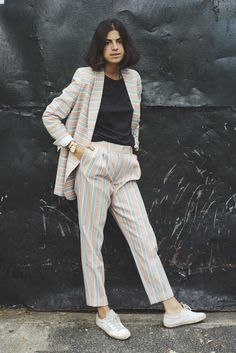 Man Repeller Leandra Medine wears a black T-shirt and white lowtop sneakers with this striped suit