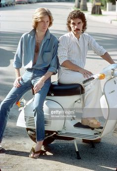 Musicians and singers Daryl Hall (L) and John Oates of the rock duo Hall & Oates pose for a portrait on a Vespa scooter in June 1976 in Los Angeles, California.