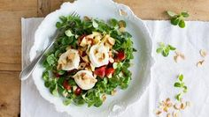 Ziegenkäsescheiben liegen auf Tomatenstücken und Feldsalat auf einem Teller.