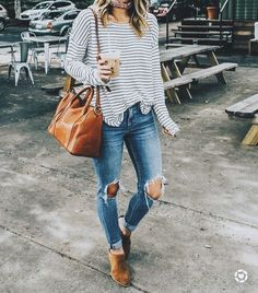 Cute striped top with distressed denim jeans, tan booties and handbag.