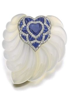 Chalcedony, sapphire and diamond brooch, Suzanne Belperron, 1942. The heart-shaped sapphire framed with calibré-cut sapphires and circular-cut diamonds, inset to a carved chalcedony mount in the form of a leaf. #Belperron #retro #brooch