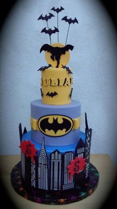This Awesome Batman Cake features the Gotham cityscape, Batman's utility belt, and a silhouette of Batman.