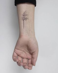 Hand poked windy tree tattoo on the wrist.