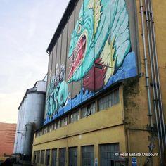 """Cosa ci fa un murales di un mostro marino gigante sulla facciata di un ex mangimificio? Quello che vedete, in questo nostro scatto, è l'ex mangimificio Martini di Ravenna, meglio conosciuto come Mosa. Il murales, comparso nel 2011, è semplicemente l'emblema della candidatura della città come """"Capitale Europea della Cultura"""". L'edificio è tuttora considerato un'archeologia industriale da tutelare."""