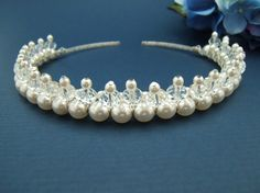 created using 8mm barrel crystal beads and 4mm white glass pearls attached to a silver toned tiara band and measures 3/4 of an inch high.