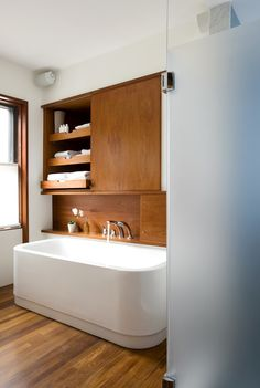 Brookline, Massachusetts residence by Butz+Klug Architecture | Clean and minimal. Woodwork and white. Deck-mounted bath fixtures. Shelf over the tub. Hidden storage. Awesome pullouts.