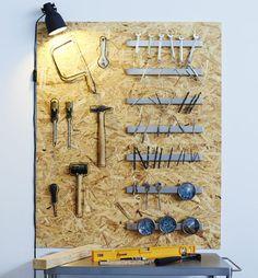Dřevěná deska za pracovním stolem, na ní magnetické lišty se šrouby, hřebíky a vrtáky...