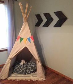 tipi interieur pour endant, une guirlande de triangles en papier multicolores au dessus de l entrée, coussins, modèle de tente indienne