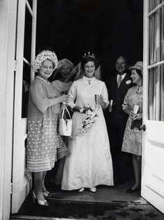 The Queen Mother, Queen Elizabeth stands with the bride at the Hornby-Cazalet wedding.