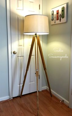 Create an industrial floor lamp for a fraction of the cost from trendy home decor stores by repurposing a vintage surveyor's tripod.