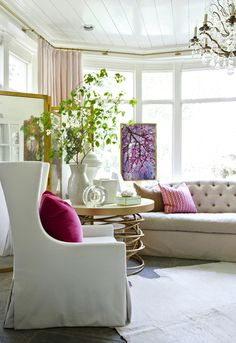 Design by Melanie Turner -- that chair, hits of color (shades of pinks, reds and purples), continuous curtain rod around the room (genius!), the table, the flood of white and bright and light. Those little bits.