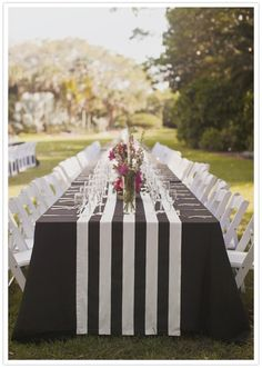 black and white stripe table runner---too thick of a runner, and obviously the wrong color, but here's an idea how the tables could look with a dark table cloth, a striped runner, and white chairs.