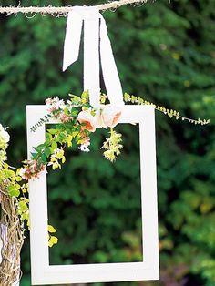 Cadre en bois peint en blanc et décoré de fleurs pour faire des portraits d'invités le jour du mariage
