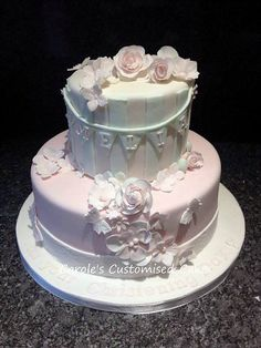 A two tier Christening cake with handmade sugarpaste lowers