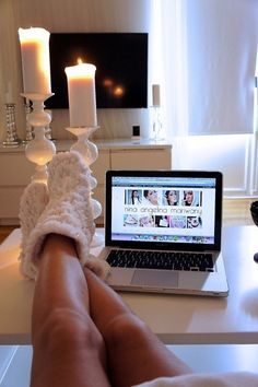 Cozy boots, laptop, candles. Comfy feel.