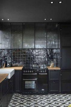 Nos encanta esta cocina en negro con #azulejos hidráulicos en el suelo y otros de formato cuadrado como revestimiento. - Imagen de Pinterest.