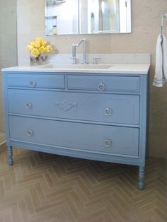 Antique dresser made into bathroom vanity. Painted blue with marble top.
