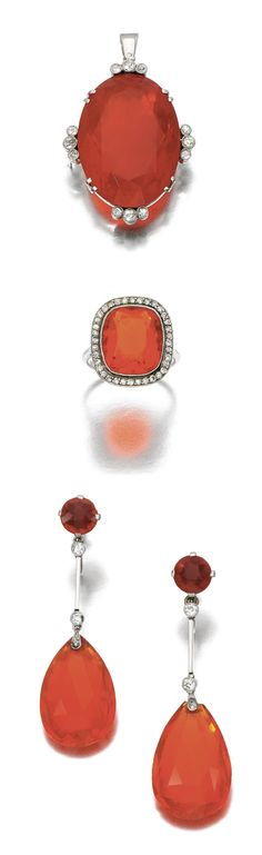 FIRE OPAL AND DIAMOND PARURE, 1920S.  Comprising: a pendant centring on an oval fire opal accented with trefoils of circular- and single-cut diamonds, to a later curb link chain; a pair of pendent earrings each suspending a facetted pear-shaped fire opal to a circular-cut fire opal surmount with baton connecting bar and circular-cut and rose diamond accents and a ring set with a cushion-shaped fire opal within a surround of single-cut diamonds