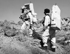 Astronauts study the geology on the atomic craters while carrying mock-ups of space backpacks and other gear.